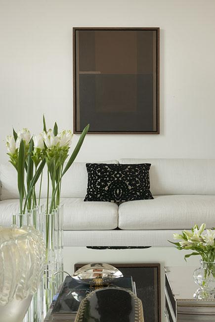 A sobriedade da moldura e tela marrom e preto sofre um contraponto pelo enorme quadrado em tons acolhedores e quentes do alaranjados do quadro colocado ao lado oposto.